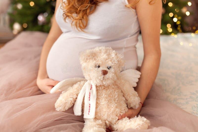 Mujer embarazada que se sienta en la cama imagen de archivo libre de regalías