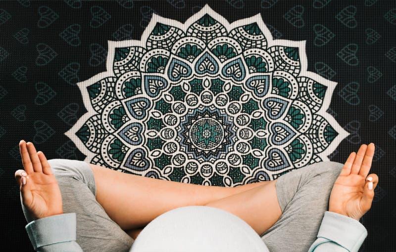 Mujer embarazada que se sienta en la posición de loto respecto a la estera y a meditar de la yoga de la mandala Visión superior fotografía de archivo