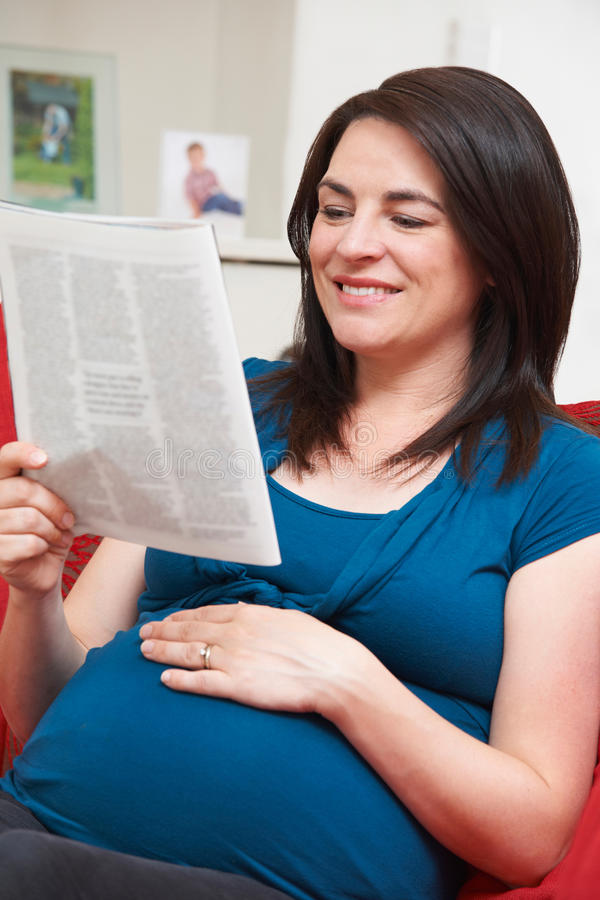 Mujer embarazada que se sienta en Sofa Reading Magazine imagen de archivo libre de regalías