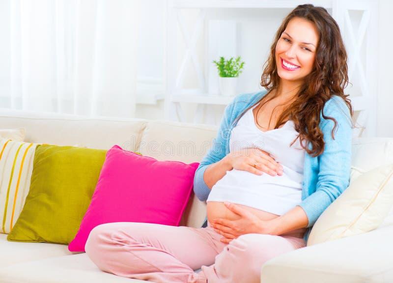 Mujer embarazada que se sienta en un sofá imagenes de archivo