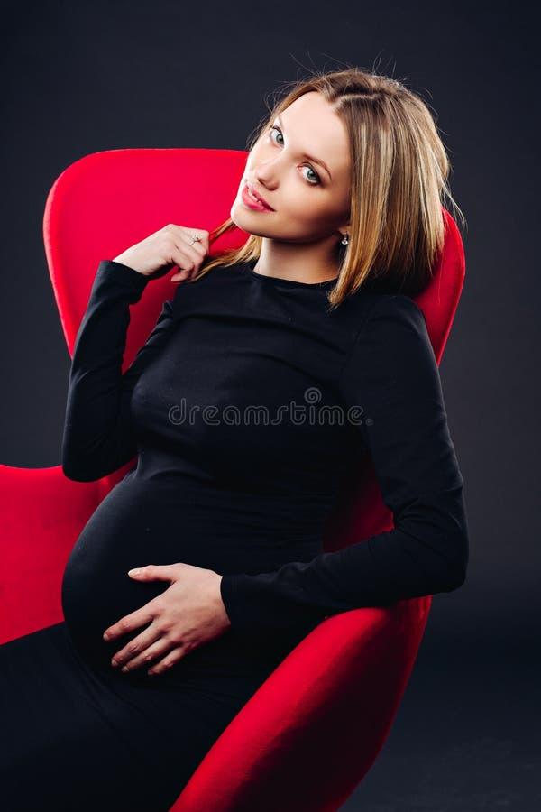 Mujer embarazada que se sostiene el vientre contra la pared negra imagenes de archivo