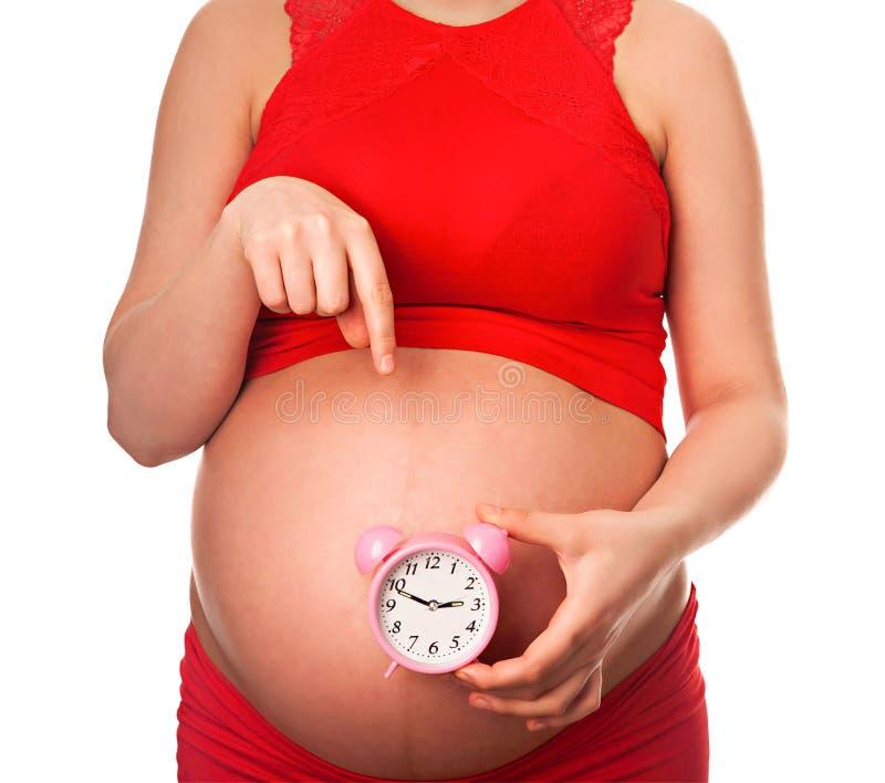 Mujer embarazada que sostiene el despertador que espera entregar pronto fotos de archivo