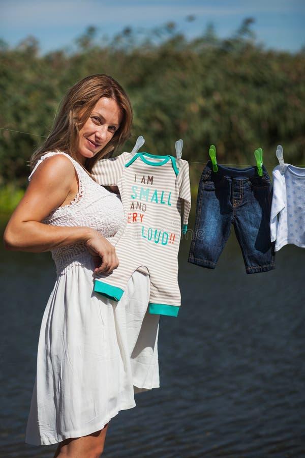 Mujer embarazada que sostiene la ropa del bebé imagenes de archivo