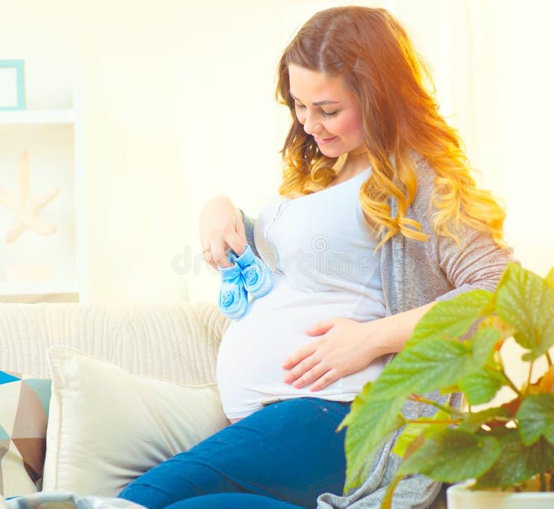 Mujer embarazada que sostiene los zapatos de bebé azul en sus manos fotos de archivo