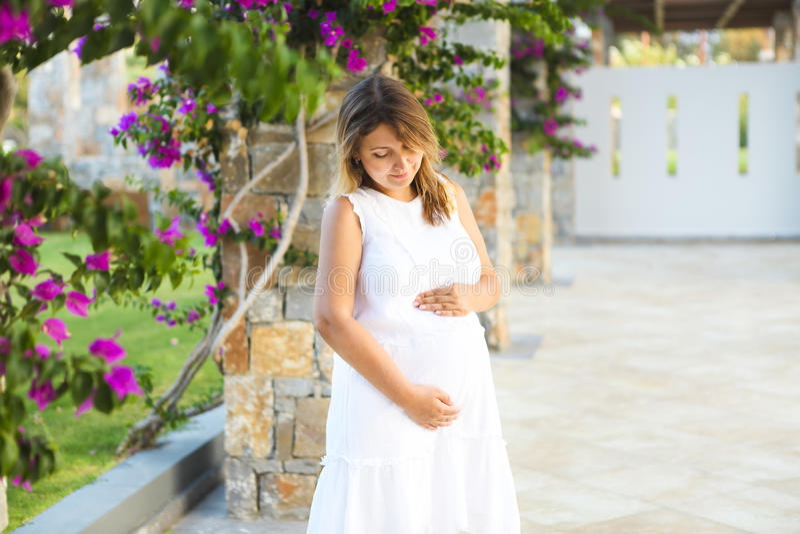 Mujer embarazada que toca su vientre con las manos fotos de archivo
