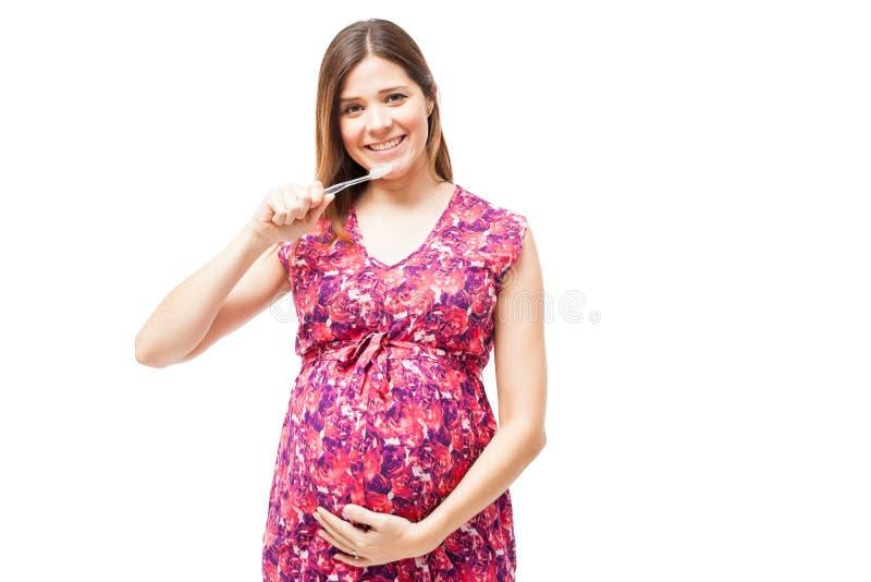 Mujer embarazada que toma el cuidado de sus dientes fotografía de archivo