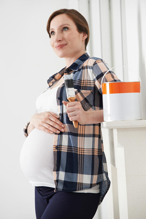 Mujer embarazada que toma la rotura mientras que adorna el cuarto de niños fotos de archivo