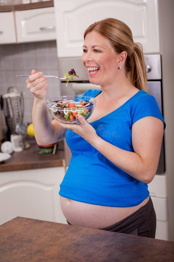Mujer embarazada sana feliz que come la ensalada vegetal foto de archivo libre de regalías
