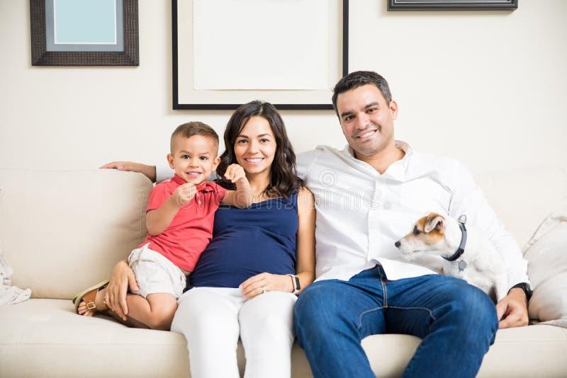 Mujer embarazada sonriente con la familia y el perro que se sientan en el sofá fotografía de archivo
