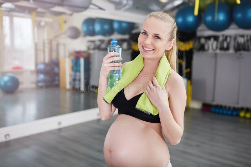 Mujer embarazada sonriente hermosa en el gimnasio que sostiene la botella y la toalla imagenes de archivo