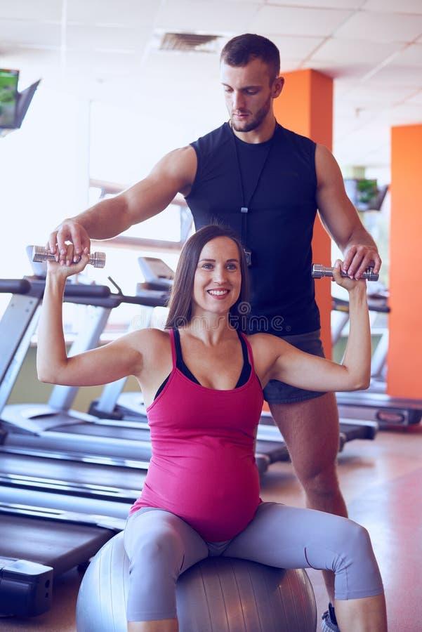 Mujer embarazada sonriente que ejercita en gimnasio con el instructor personal fotografía de archivo