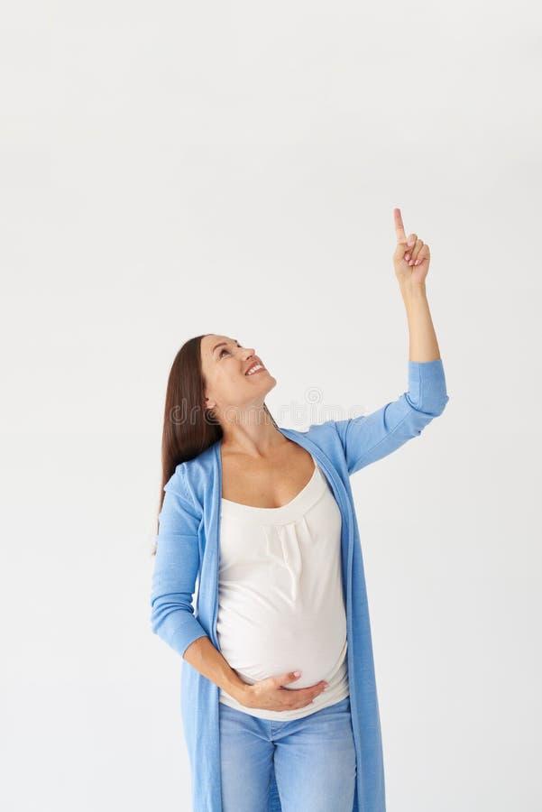 Mujer embarazada sonriente que señala el finger hacia arriba imagen de archivo