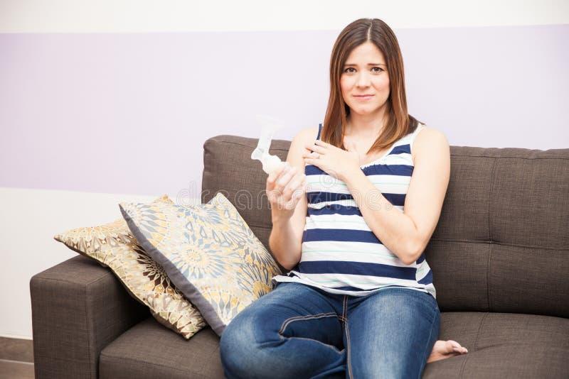 Mujer embarazada subrayada con la bomba de lactancia foto de archivo libre de regalías