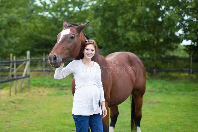 Mujer embarazada y caballo jovenes atractivos en campo imágenes de archivo libres de regalías