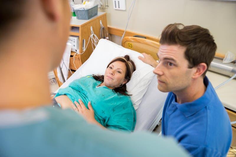 Mujer embarazada y marido que miran a la enfermera In fotos de archivo