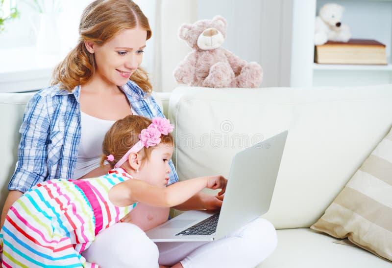 Mujer embarazada y niño de la familia feliz con un ordenador portátil en casa foto de archivo libre de regalías
