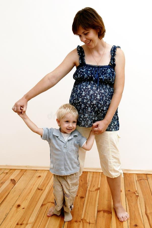Mujer embarazada y niño pequeño imagen de archivo