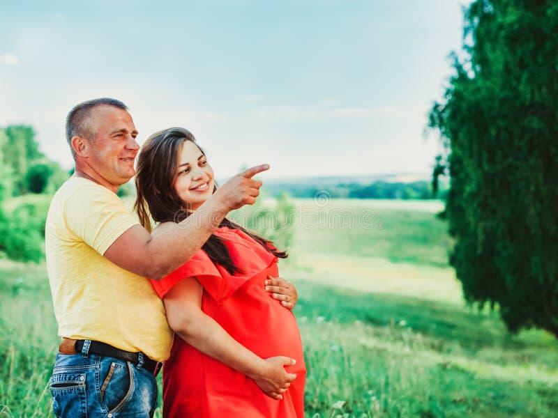 Mujer embarazada y su marido con las manos en el vientre al aire libre foto de archivo