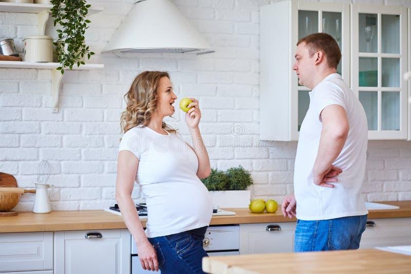 Mujer embarazada y su marido en la cocina de la casa con fruta La familia espera el nacimiento de un hijo fotos de archivo