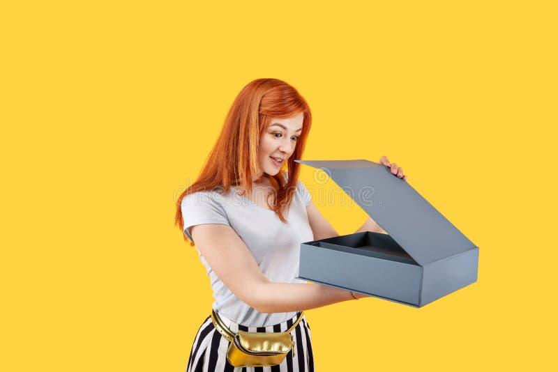 Mujer emocionada agradable que sostiene una caja fotos de archivo
