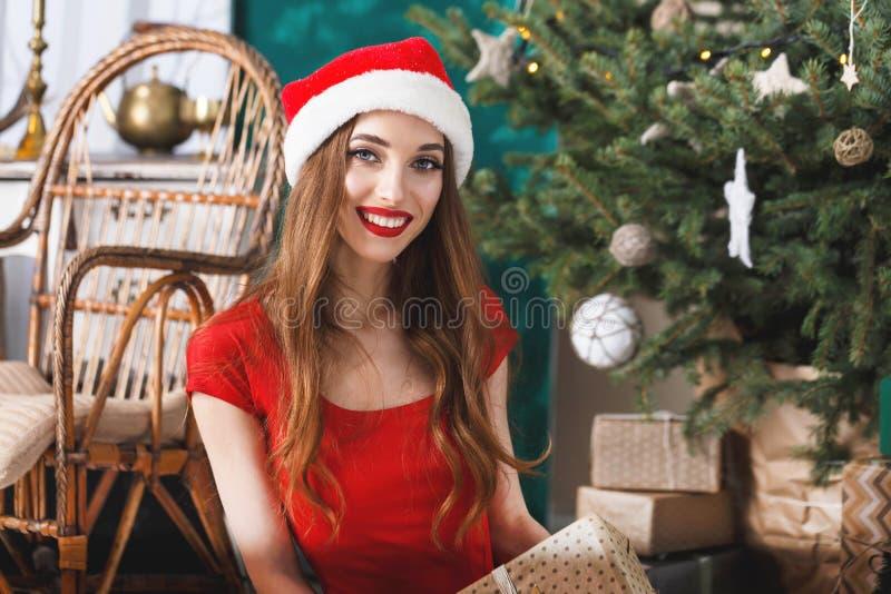 Mujer emocionada de la Navidad que lleva la picea del Año Nuevo de Santa Hat Sitting Near The fotos de archivo libres de regalías