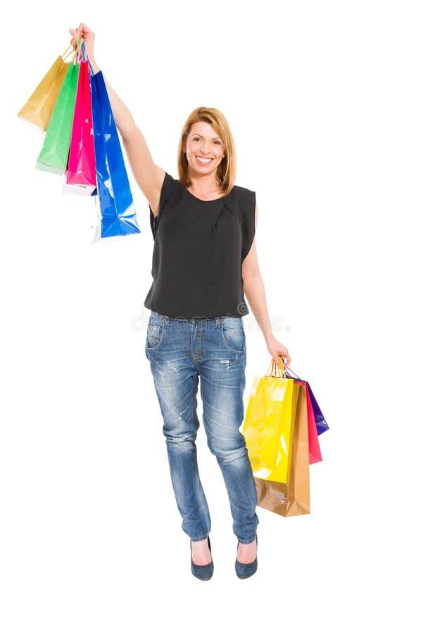 Mujer emocionada de las compras que se coloca en el fondo blanco imagen de archivo