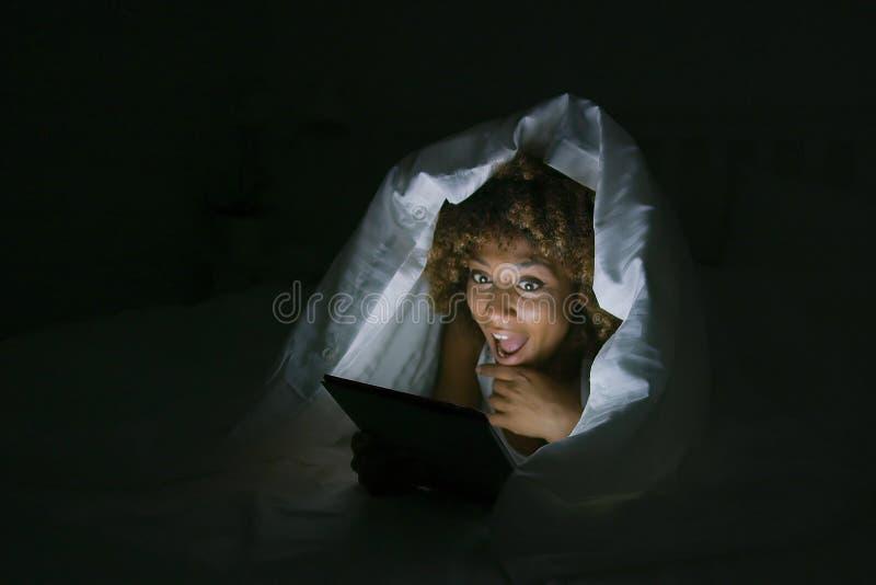 Mujer emocionada debajo de la manta con la tableta imagenes de archivo