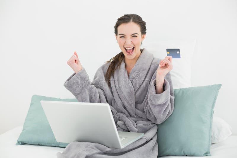 Mujer emocionada en la albornoz que hace compras en línea en cama fotos de archivo