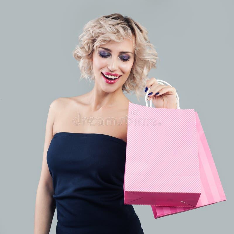 Mujer emocionada feliz que celebra bolsos que hacen compras rosados y la sonrisa foto de archivo