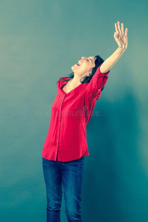 Mujer emocionada que grita con lenguaje corporal eufórico fotografía de archivo
