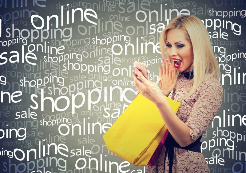 Mujer emocionada que hace compras en línea comprobando precios en el teléfono móvil Muchacha sorprendida con los bolsos coloridos foto de archivo libre de regalías