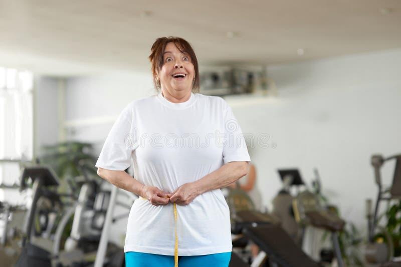 Mujer emocionada que mide su cintura en el gimnasio imagen de archivo