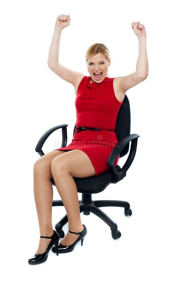 Mujer emocionada que se sienta en silla. Aislado imagen de archivo libre de regalías
