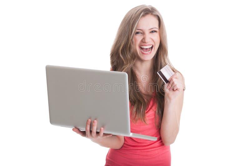 Mujer emocionada que sostiene un ordenador portátil y una tarjeta de crédito fotos de archivo libres de regalías