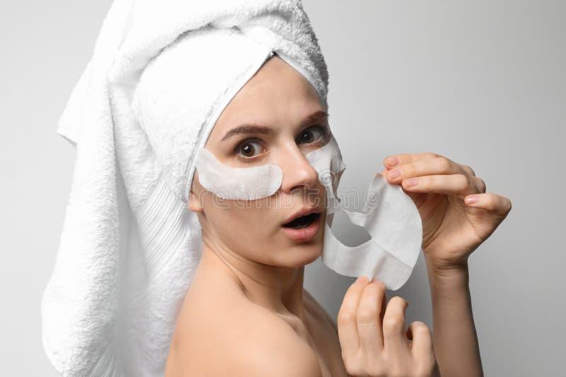 Mujer emocional con las máscaras de la cara y de ojo del algodón fotografía de archivo