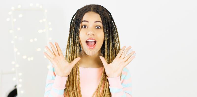 Mujer emocional negra joven del retrato con el pelo afro Fondo gris foto de archivo