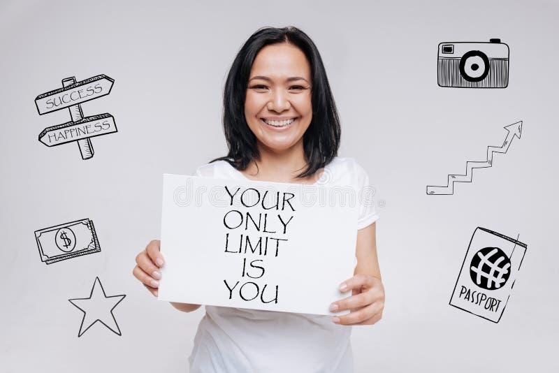 Mujer emocional que lleva a cabo un lema positivo y que sonríe feliz imágenes de archivo libres de regalías