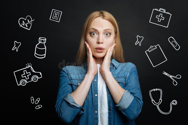 Mujer emocional que toca su cara y que parece sorprendida foto de archivo