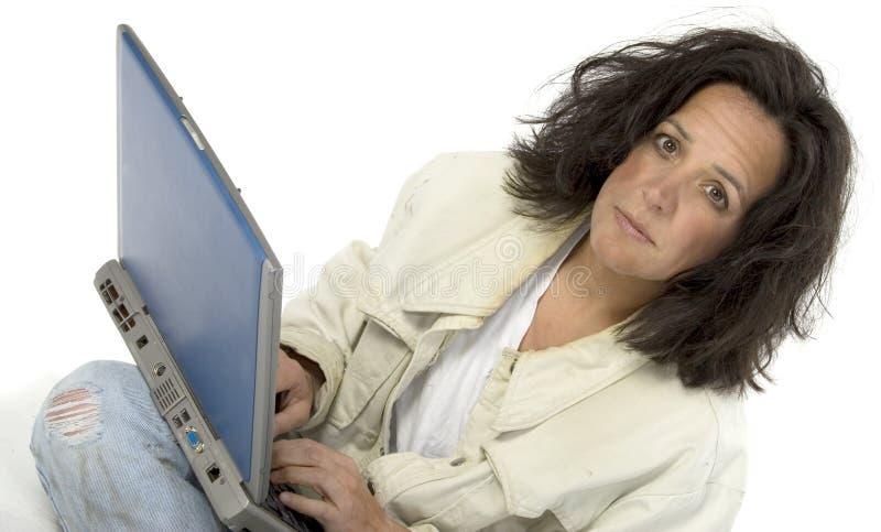 Mujer empobrecida con la computadora portátil imagen de archivo