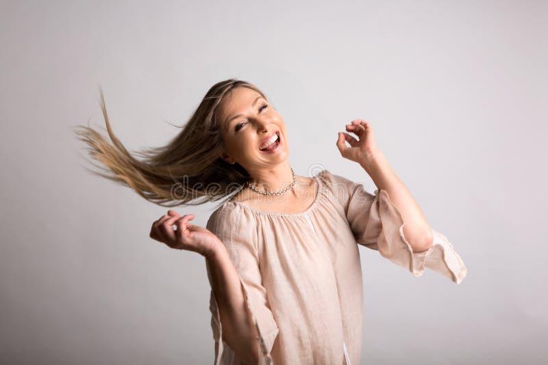 Mujer enérgica natural despreocupada sonriente que chasquea el pelo largo foto de archivo libre de regalías