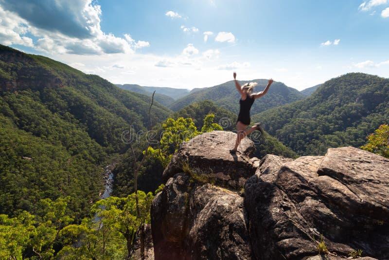 Mujer enérgica que salta en una alta repisa del acantilado imagen de archivo libre de regalías