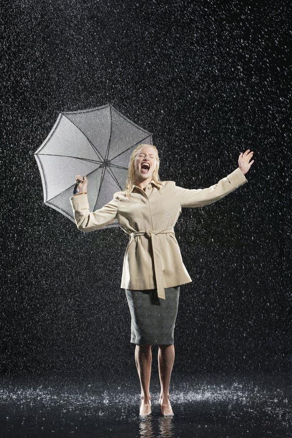 Mujer en abrigo con el paraguas que goza de la lluvia foto de archivo libre de regalías