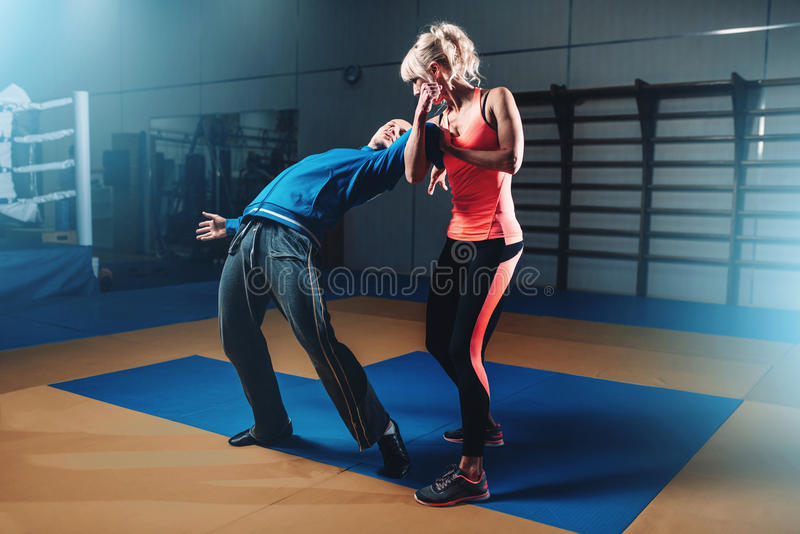 Mujer en actoin en el entrenamiento de la autodefensa imagen de archivo