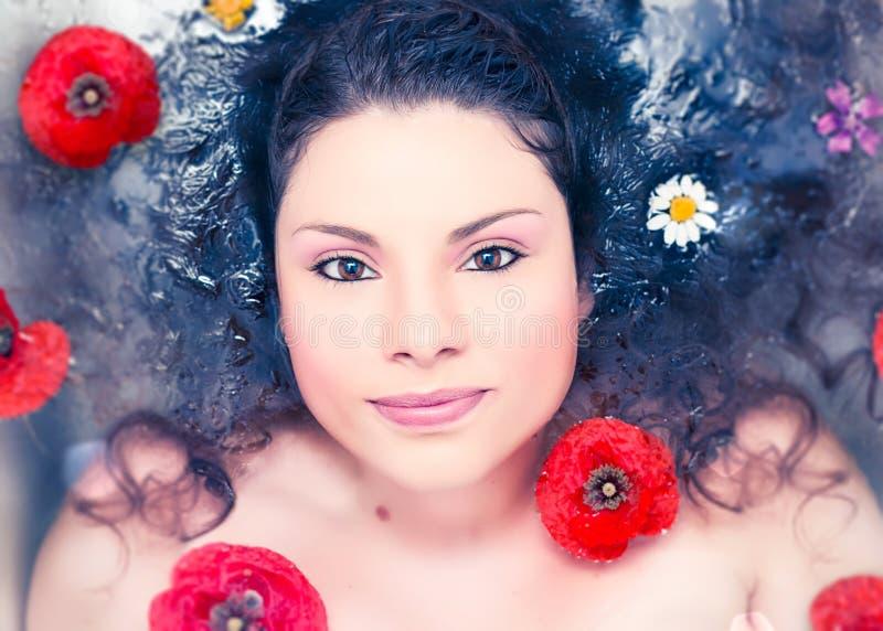 Mujer en agua con las flores fotografía de archivo