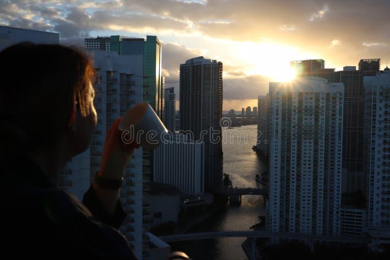 Mujer en albornoz que bebe su café o té de la mañana en un balcón céntrico Salida del sol hermosa en Miami céntrica Mujer que dis imagen de archivo
