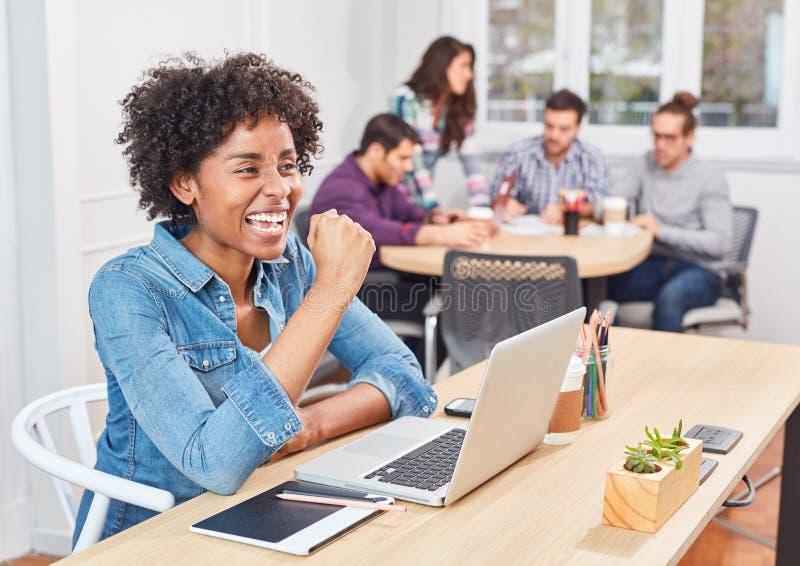 Mujer en alegrías de lanzamiento de la oficina con el puño apretado imagen de archivo