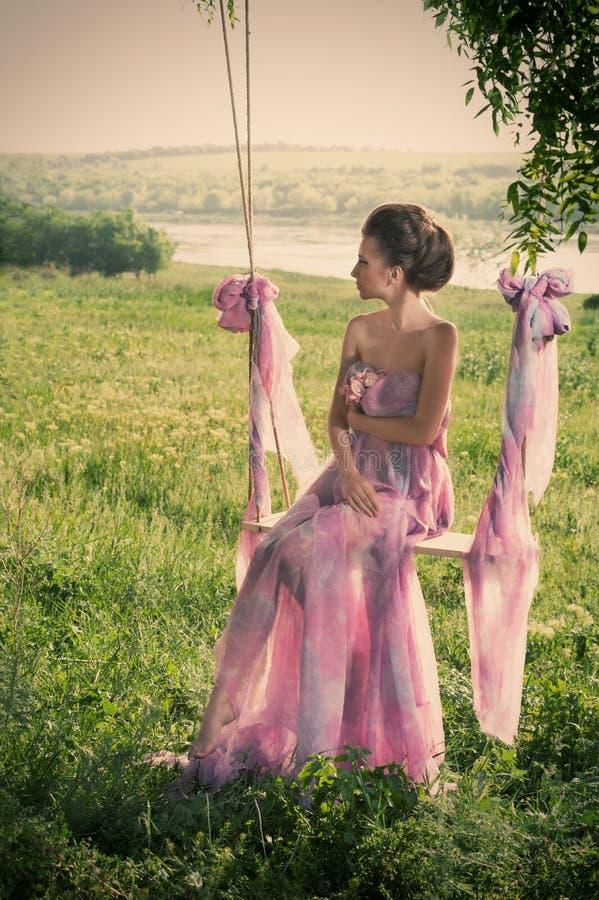 Mujer en alineada rosada airosa en los oscilaciones imagenes de archivo