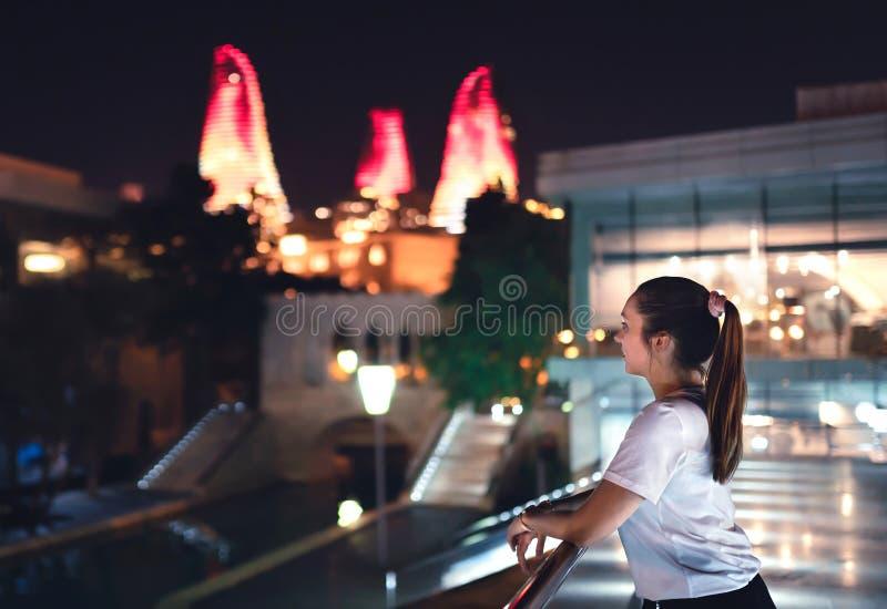 Mujer en Baku en la noche que mira las torres de la llama Turista en Azerbaijan en vacaciones Explore y visite al capital foto de archivo libre de regalías
