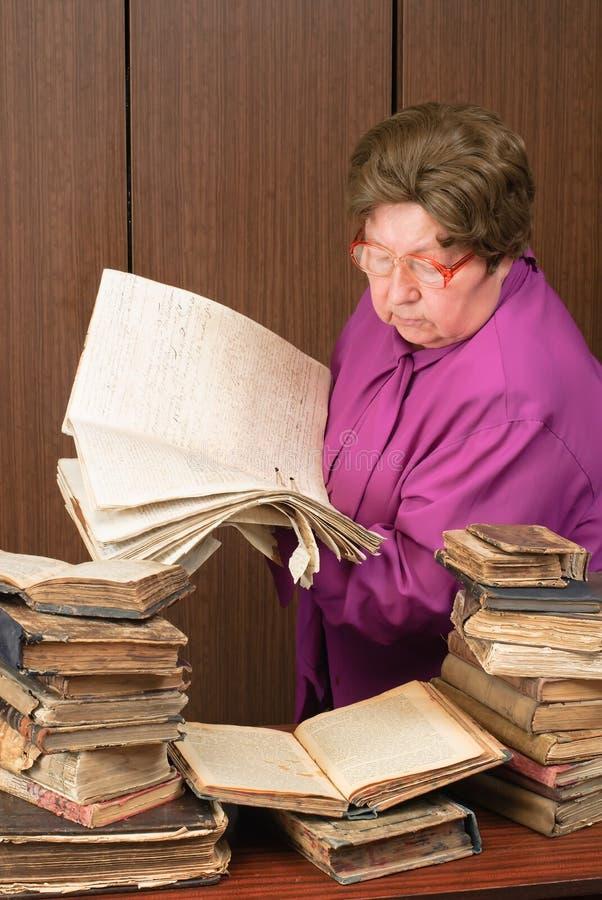 Mujer en biblioteca con los libros religiosos fotografía de archivo libre de regalías