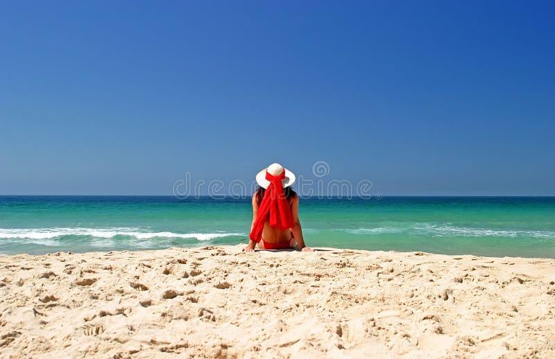 Mujer en bikiní rojo y el sombrero que se sientan en paz en una playa asoleada hermosa. fotografía de archivo
